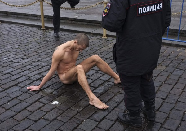 Police approach artist Pyotr Pavlensky sitting on the pavestones of Red Square during a protest in front of the Kremlin wall in central Moscow, November 10, 2013. Pavlensky nailed himself to the pavestones by his genitals as part of an art performance in protest of what he sees as apathy in contemporary Russian society and the possibility such indifference can lead eventually to a police state. The performance coincided with the day when the Interior Ministry honoured its service members.