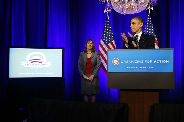 U.S. President Barack Obama (R) applauds after being introduced by volunteer Leslie Sheffield as he takes the stage for remarks on the Affordable Care Act, commonly known as Obamacare, at an Organizing for Action grassroots supporter event in Washington in this November 4, 2013, file photo.