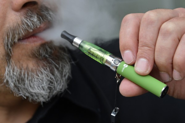 Gabor Kovacs of 'smoke no smoke' puffs on an e-cigarette that his shop sells in London in this June 9, 2013 file photo.