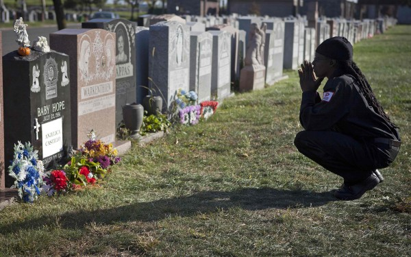 Latisha Berkley, a cemetery security guard, kneels and prays at the tombstone of Anjelica &quotBaby Hope&quot Castillo in the Bronx borough of New York, in October. Anjelica Castillo's name has since been engraved on her tombstone, which was originally paid for by  New York detectives.
