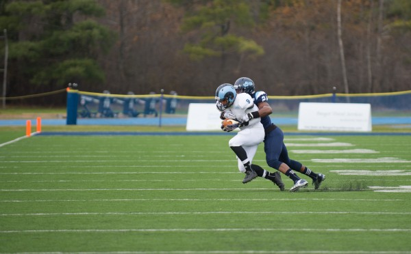 The University of Maine's Khari Al-Mateen tackles the University of Rhode Island's Andrew Matos in Saturday's game held at Alfond Stadium in Orono. The Black Bears won 41-0 and are the CAA football champions.
