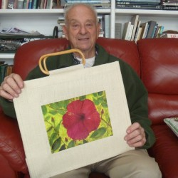 Artist Norm Stern of Hampden holds a totebag bearing an image of his original painting of a hibiscus. Stern's totebags will be available for purchase at the Congregation Beth Israel Sisterhood annual Holiday Marketplace and Craft Fair 11 a.m.-3 p.m. Sunday, Nov. 17, at 144 York St.
