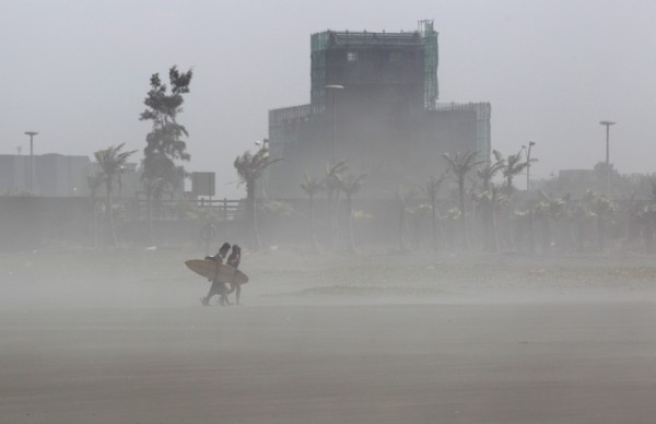 Surfers walk as strong wind brought by Typhoon Soulik kick up sand around them as the typhoon approaches the northeastern harbour of Wushih in Ilan county July 11, 2013.
