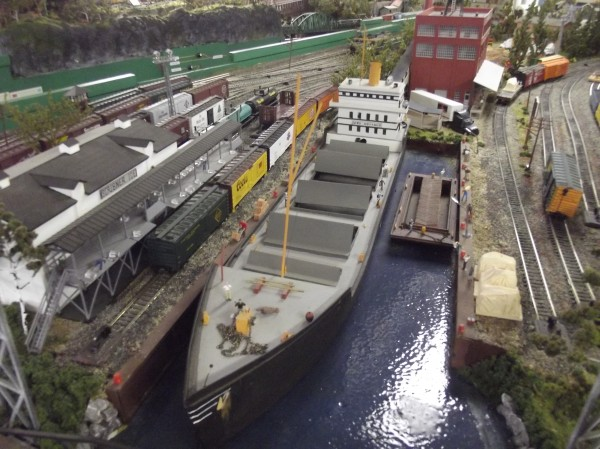 The railroad layout includes intricate scenes like this one of a ship in port.