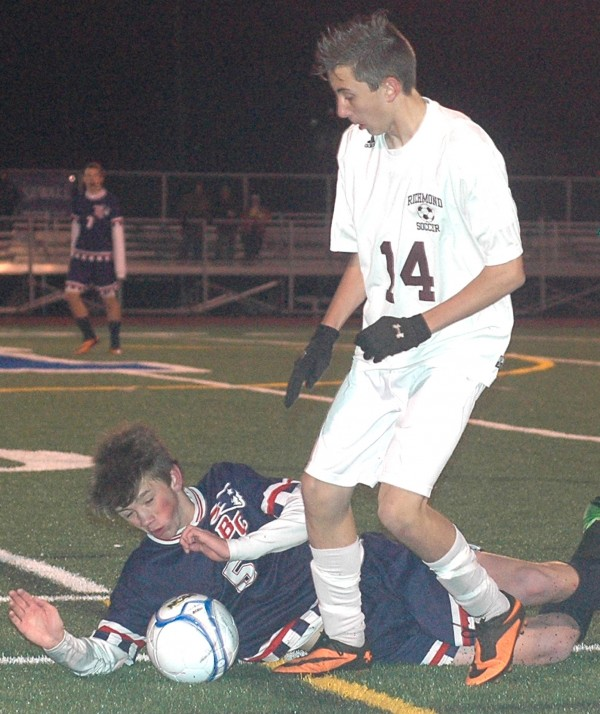 Bangor Christian striker Brandon Messer (5) takes a tumble while battling with Richmond's Cody Tribbett during the state Class D final at McMann Field in Bath on Saturday. Messer and his Patriot teammates won in penalty kicks, 2-1, for their fifth straight Class D title.