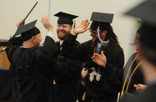 Inmates Jon Brent Dyer, left, Jerry James Banks, center and Brandon Brown celebrate getting diplomas from the University of Maine at Augusta during a ceremony on Monday at the Maine State Prison.