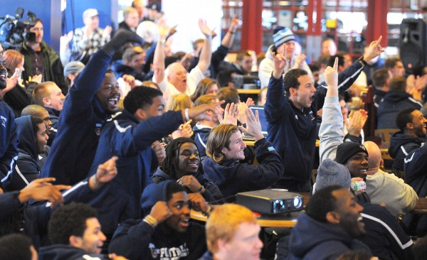 University of Maine football players cheer as they learn of their postseason berth in the upcoming NCAA Tourney.  Players staff and fans gathered Sunday morning at the Orono campus's Memorial Union to watch the television broadcast