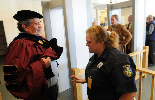 Thomas Abbot, a dean at the University of Maine at Augusta, gets screened by corrections officer Angela Smith at the Maine State Prison on Monday before  graduation ceremonies for 14 inmates earning degrees from UMA.