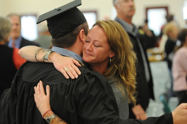 Inmate Steven Clark gets a hug from his girlfriend Tomi Doyle after Clark received his associates degree from the University of Maine in Augusta on Monday at the Maine State Prison.