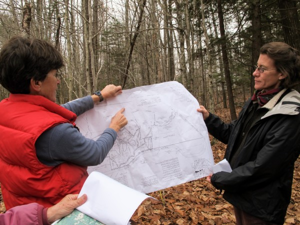 Ann Flannery (from left), the former landowner of a 29-acre parcel of land in Topsham recently acquired by the Brunswick-Topsham Land Trust, looks at a map of the land while surveying the property with Julie Isbill of the National Park Service.
