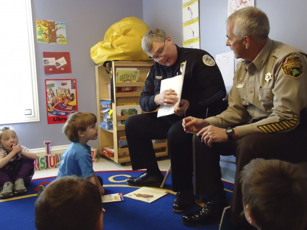 Houlton Police Chief Butch Asselin (center) and Aroostook County Sheriff Jim Madore read a book to children in the early learning program at the Houlton Head Start Center.