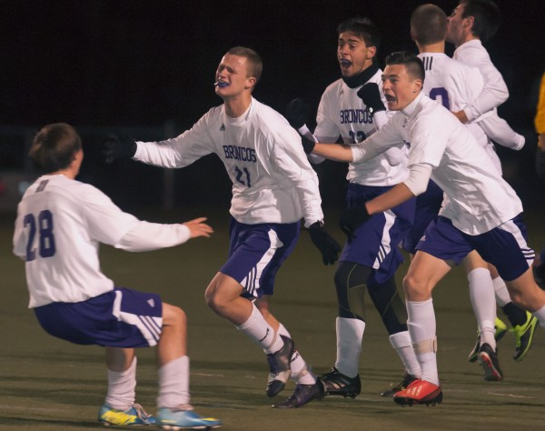 Hampden Academy soccer player Tristan Gardner (21) is mobbed in celebration by his teammates after scoring the winning goal in overtime in the Eastern Maine Class A soccer championship against Lewiston in Hampden on Wednesday, Nov. 6, 2013.