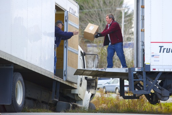 Packages are transferred from a CDS Delivery truck after a Stewart's tow truck carrying a Pine Tree Services truck, both from Orrington, collided with the truck Friday morning near the intersection of Banair Road and Hammond Street Extension in Bangor.
