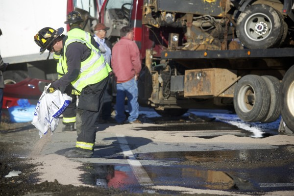 A firefighter pours absorbent material onto fluids that covered the ground.