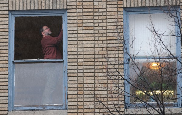 Licensed Massage Therapist Eric Sirois inspects the window frame where a sheet of glass once was until wind pulled the glass out and sent it to the sidewalk three stories below. No was one injured when the glass fell.