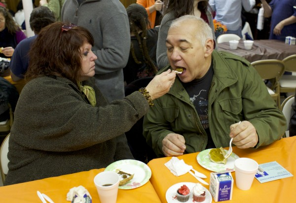 From left, neighbors Anna Royal and Keith Kline share pie during a free Thanksgiving meal served by Manna Ministries and volunteers Thursday morning at Columbia Street Baptist Church in Bangor.