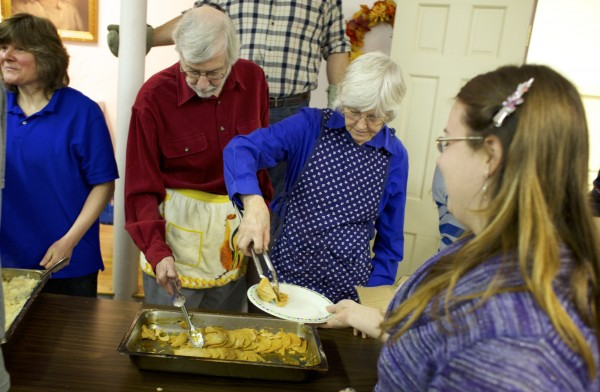 From left, Tom and Kathy Taylor serve turkey during a free Thanksgiving dinner provided by Manna Ministries Thursday morning at Columbia Street Baptist Church in Bangor.