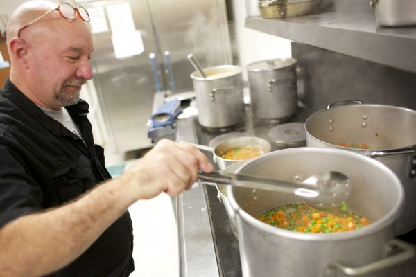 Kirk Swenson cooks peas and carrots Thursday morning at Columbia Street Baptist Church before volunteers served a free Thanksgiving meal from Manna Ministries in Bangor.