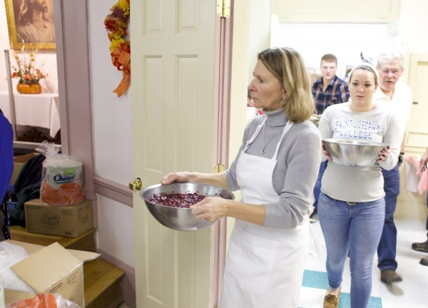 Pat Parker brings out cranberry sauce Thursday morning while serving a free Thanksgiving meal from Manna Ministries Thursday morning at Columbia Street Baptist Church in Bangor.