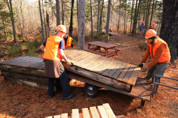 Members of Maine Conservation Corps stack sections of the Orono Bog Boardwalk deemed fit for salvage on Saturday.