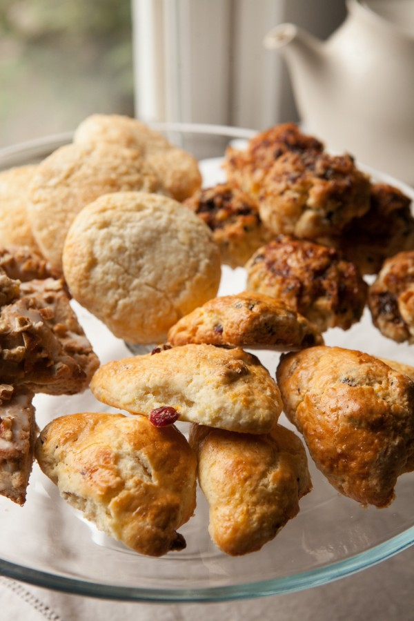 An assortment of scones including Orange and Cranberry Scones, Tiny Buffalo's Fig and Mascarpone Scones, classic scones, and Tiny Buffalo's Apple-Pecan-Cinnamon Scones.