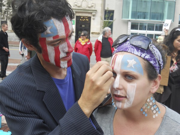 Travis Bonpietro, 24, of Gorham, paints the face of Rose Buckmore, 21, of Portland before their group, Occupy Maine, sets out on a march from Monument Square to the University of Southern Maine campus and back in Oct. 2011.