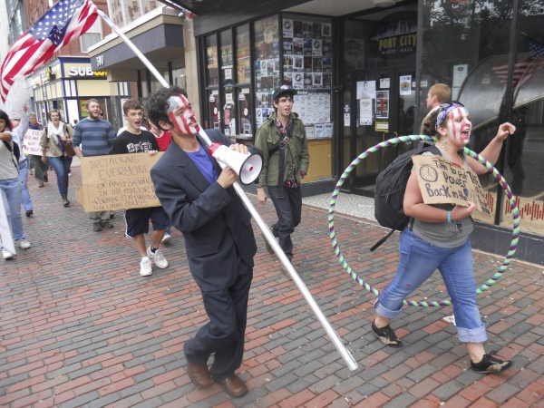 Travis Bonpietro, 24, of Gorham, and Rose Buckmore, 21, of Portland, lead a crowd of more than 60 people marching from Monument Square in Portland to University of Southern Maine in Oct. 2011. The marchers chanted things such as &quotHow do we end the deficit? End the war and tax the rich,&quot and &quotBanks got bailed out, we got sold out.&quot