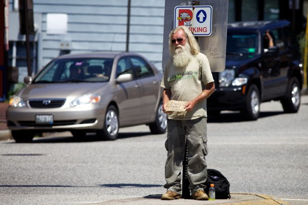 A man, who did not want to give his name, asks for spare change in the median strip at St. John Street and Congress Street in Portland in July.