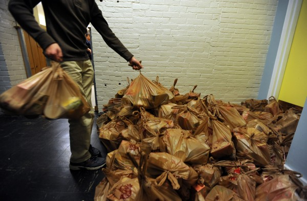 Volunteer Lucas Seavey adds more bags containing, stuffing, gravy, cranberries, pie mix and veggies to a growing stock pile at Manna that will be handed out along with a frozen turkey to hundreds of needy families on Monday.