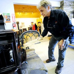 Gary Asselin feeds a log into a high-efficiency wood-burning Jotul stove at his Auburn store, Fireside Stove Shop. The federal Environmental Protection Agency is tightening standards for wood-stove emissions. Changes are expected next year.