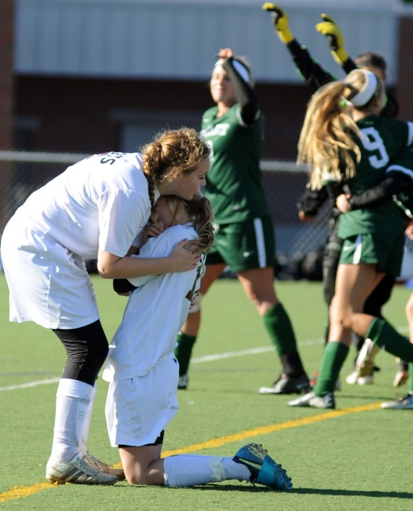 Orono's Kate Ferguson (left) and Brinsley Chasse hug after being defeated 3-2 in double overtime by Waynflete in the girls Class C State Championship game on Saturday in Hampden.
