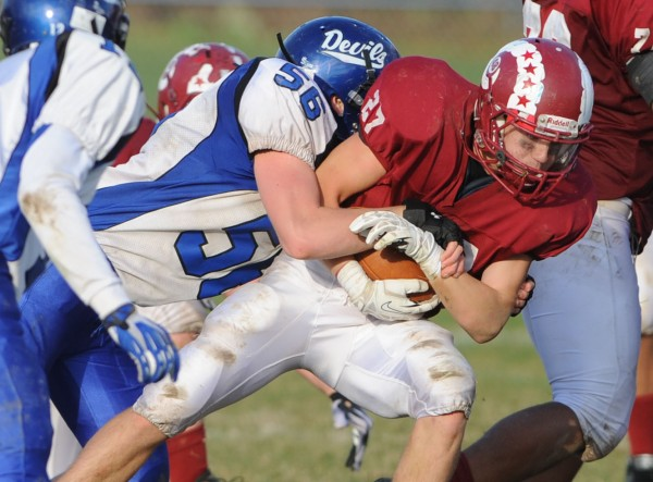 Bangor's Logan Lanham is brought down by Lewiston's Sabin Lavorgna during third-quarter action Saturday at Bangor.