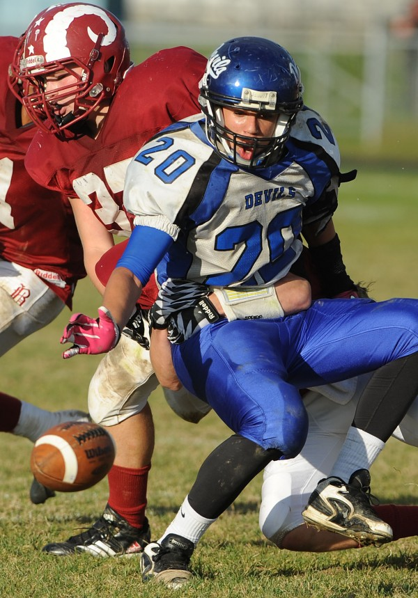 Lewiston's Matt Hudson has the ball knocked from his grip by Bangor's James Deane and Evan McAuliffe during third-quarter action Saturday at Bangor.