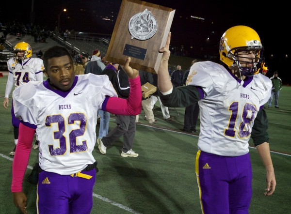 Josh Gray (left) and Nicholas Bishop of Bucksport High School hoist their runner-ip plaque Saturday after the Class D state football final at Portland's Fitzpatrick Stadium. Oak Hill beat Bucksport 42-35 to garner its first state football title in 31 years.