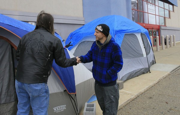 Fellow campers Tony Avitar, left, and Jonas Allooh greet each out at their tents outside of a Best Buy store on Nov. 19, 2013, in Cuyahoga Falls, Ohio, as they hopes to be one of the first through the doors to score Black Friday shopping bargains.
