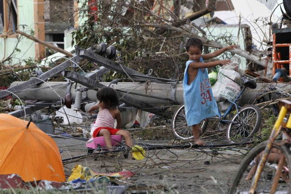 Children play near electric posts Saturday after Typhoon Haiyan battered Tacloban city in the central Philippines on Friday.
