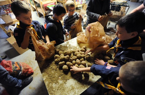 Boy Scouts from Pack 6 Bangor Wolf Den along with their siblings fill bags with potatos in the basement of Manna on Saturday as Manna Ministries prepares to distribute Thanksgiving dinners to hundreds of needy families in the area on Monday.