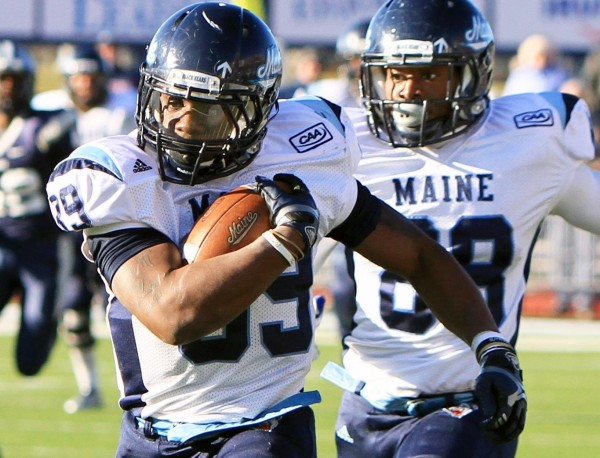 The University of Maine's Rickey Stevens carries the ball for yardage during the third quarter of Saturday's game against University of New Hampshire at Cowell Stadium in Durham.  At right is teammate Damarr Aultman.