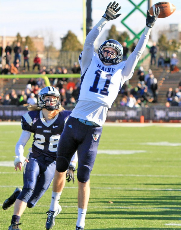 University of New Hampshire defender Casey DeAndrade nears University of Maine's John Ebeling as he jumps to catch a pass during Saturday's game.