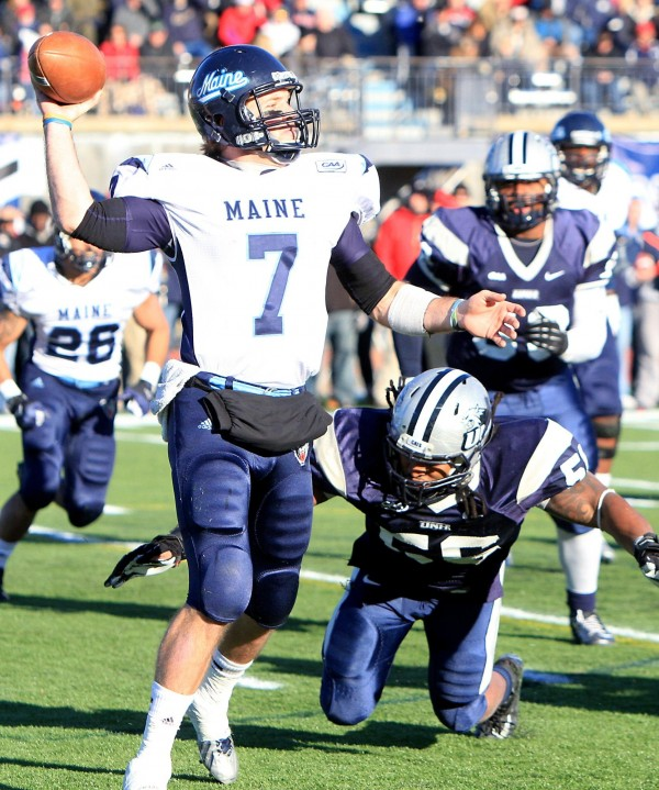 University of Maiine quarterback Marcus Wasilewski looks to pass while University of New Hampshire linebacker DeVaughn Chollete attempts a sack during Saturday's game at Cowell Stadium in Durham.