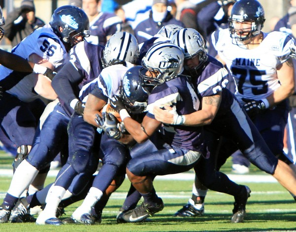 University of New Hampshire defenders take down University of Maine's Rickey Stevens during Saturday's game in Durham.