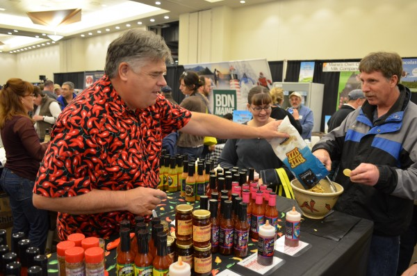 Dan Stevens (left), owner of Captain Mowatt's of Portland, pours chips so a patron can try one of 17 varieties of his company's hot sauce at the Maine Harvest Festival at the Cross Insurance Center in Bangor on Saturday, Nov. 16. The event continues Sunday.