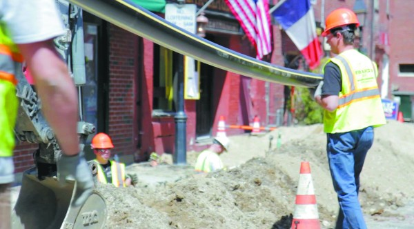 Workers for the natural gas company Unitil carry high-density plastic piping to a trench in the Old Port during early stages of the company's 14-year, $60 million infrastructure project.