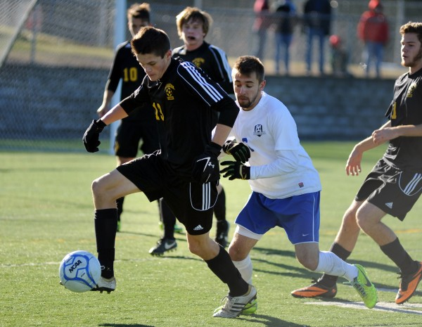 Maranacook's Jake Hebert drives the ball by Madawaska forward Kodey Lolmitz in first-half action of the Class C boys state championship game at Hampden on Saturday.