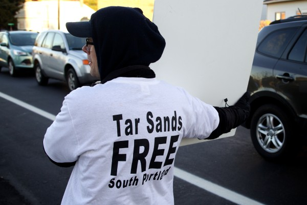 Sylvia Schlotterbeck of Auburn holds a sign outside the polls on Broadway in South Portland seeking votes in favor of the waterfront protection ordinance that would prevent tar sands oil from flowing to the Portland-Montreal Pipe Line.