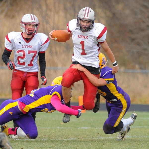 Mattanawcook Academy quarterback Trysten Pelkey (center) scrambles for yardage as he is tackled by Bucksport High School's Asher Bowden (left) and Nic Bishop during the Eastern Maine Class D championship game in Bucksport on Saturday.