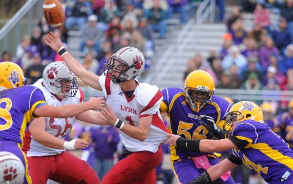 Mattanawcook Academy  quarterback Trysten Pelkey (center) fires off a pass while under pressure from Bucksport High School players during the Eastern Maine Class D championship game in Bucksport on Saturday. The Golden Bucks won the game 42-8.
