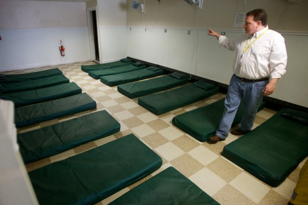 Josh O'Brien, director of Portland's Oxford Street Shelter, counts matts on the floor at the facility Wednesday Dec. 12, 2012 during his daily walk through.