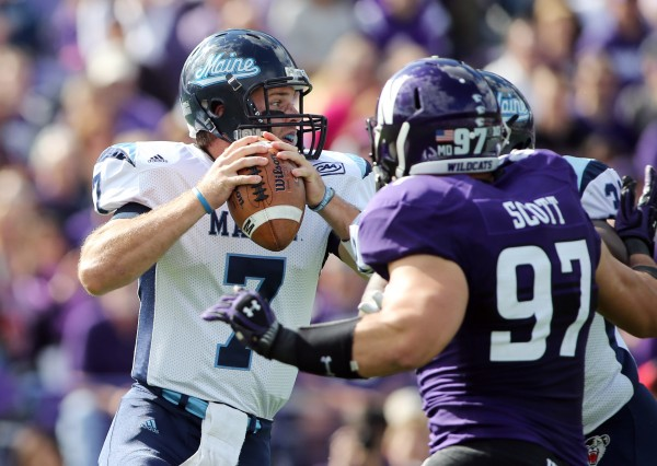 Black Bears quarterback Marcus Wasilewski looks for a receiver while pressured by Northwestern's Tyler Scott (97) during their game on Sept. 21 in Evanston, Ill. Wasilewski rallied Maine to a 19-14 victory over Stony Brook during their CAA game in Orono Saturday.