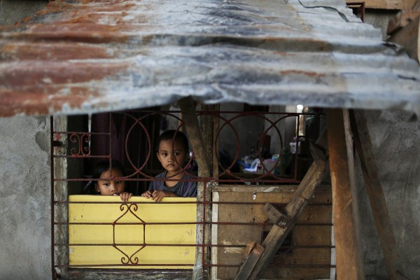 Children look out from their house, which was damaged by Typhoon Haiyan, south of Tacloban on Nov. 16, 2013.